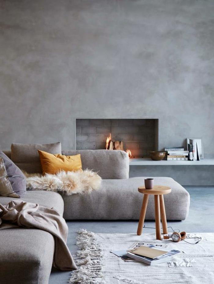 couleur assortie au gris, petit tabouret en bois, enduit mural gris, sofa bas