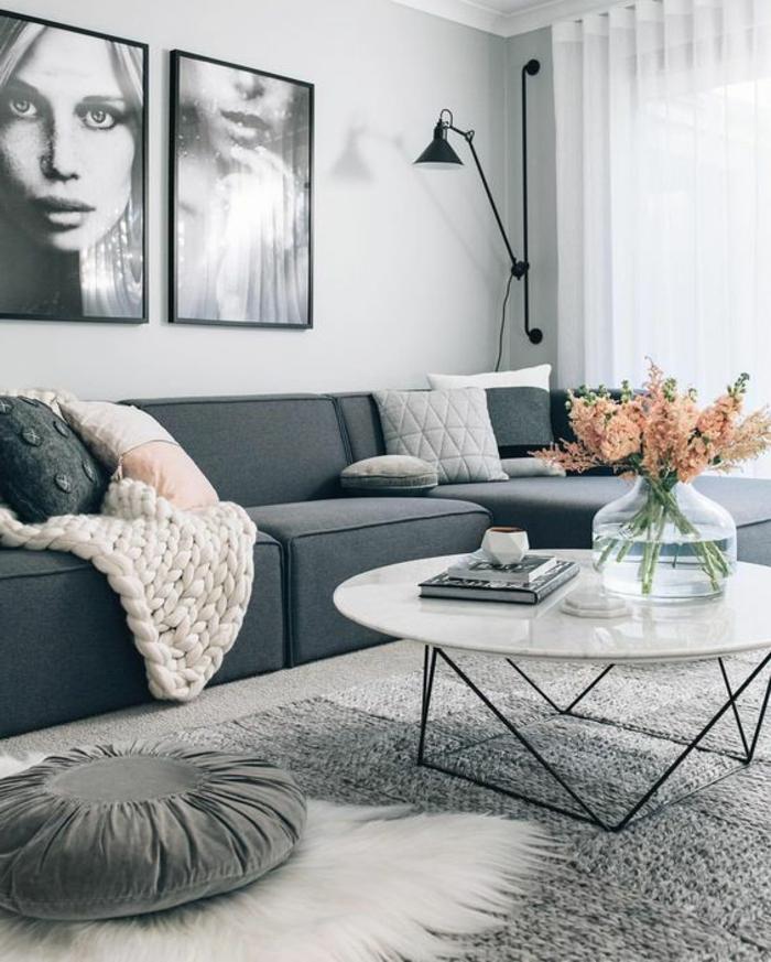 couleur assortie au gris, table blanche ronde, portraits en noir et blanc, plaid rose tricoté