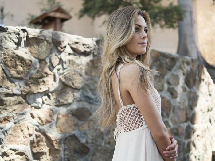 balayage blond, robe blanche, manucure français en rose, mur en pierre, cheveux longs, couleur blonde