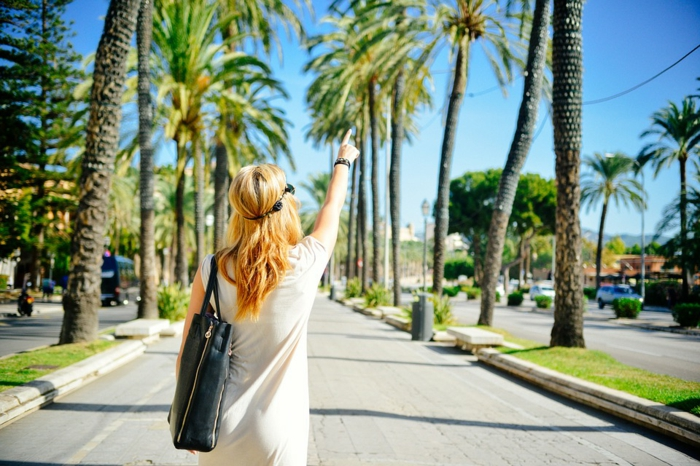 balayage blond, palmes, sac à main en cuir noir, robe blanche, couleur blonde, couronne en fleurs noires, meche blonde