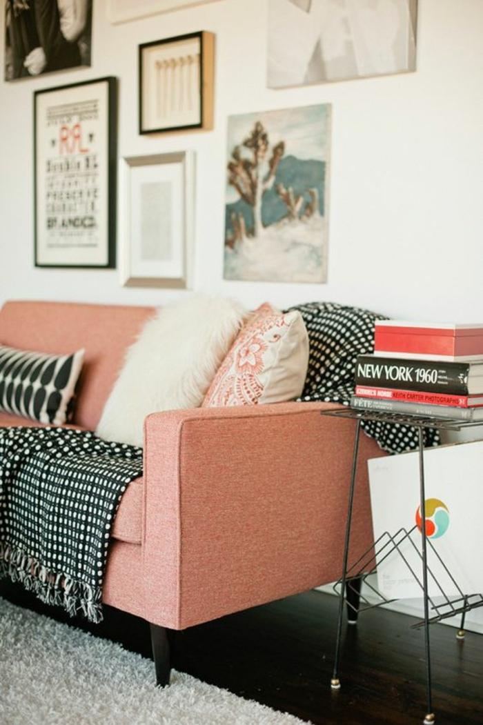 sofa couleur corail, coussins, tableaux encadrés, murs blancs, chevet avec des livres