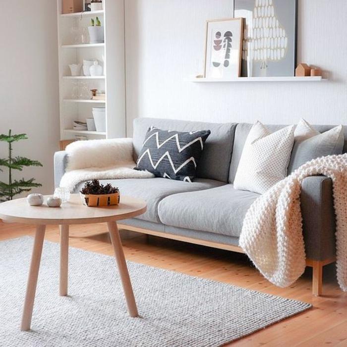 couleur qui va avec le gris, petite table ronde, sofa gris, jeté de lit rose, porte-cadre blanc et étagère blanche