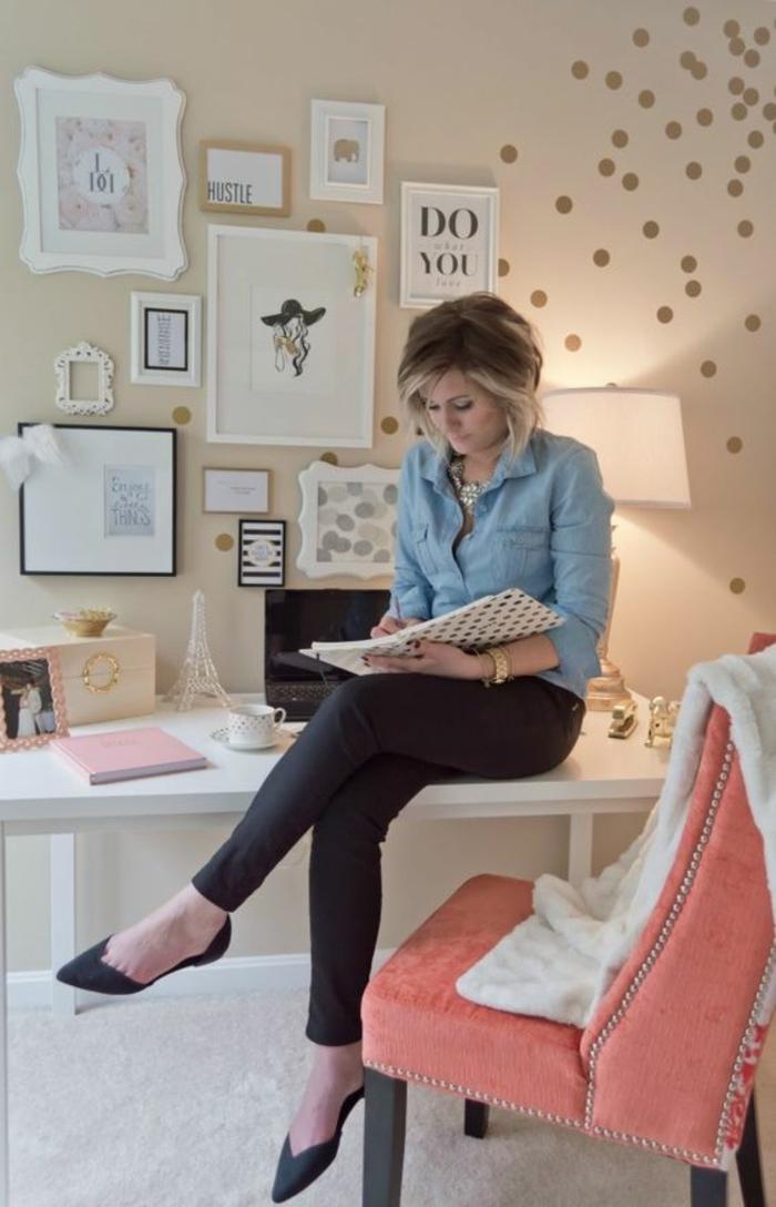 fauteuil couleur saumon, table blanche, papier peint couleur pêche, tableaux encadrés