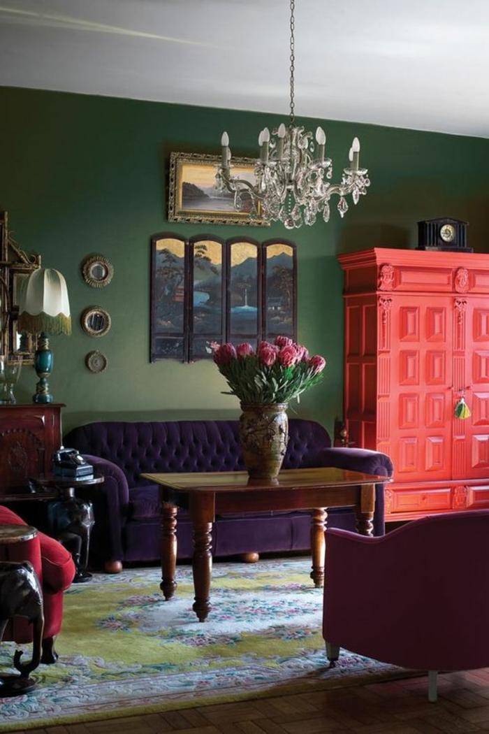 armoire couleur saumon, chandelier pampilles, sofa lilas, table vintage, mur vert sombre