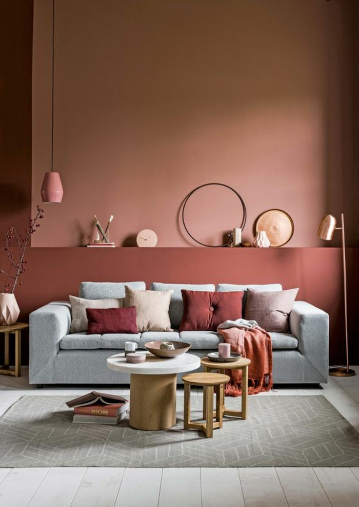 mur couleur saumon, sofa gris, table basse, tabourets de bois, lampe pendante rose