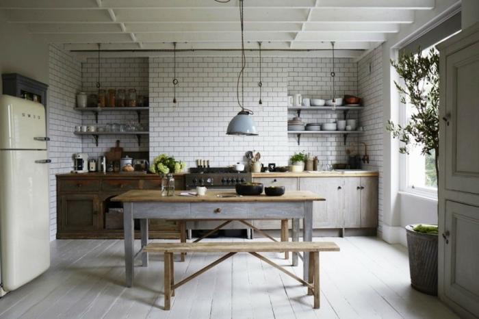 modele de cuisine, grand pot à fleur en béton, banc en bois, mur en briques peint en blanc, cuisine aménagée