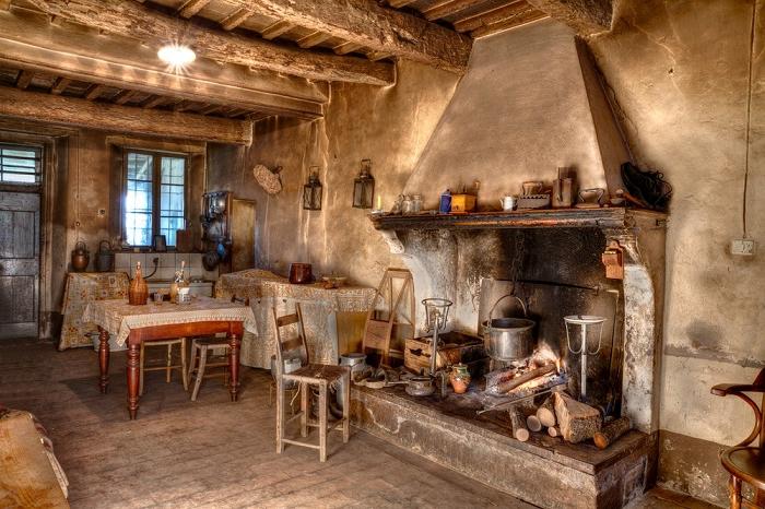 cuisine rustique, cheminée en béton, casserole, fenêtre à carreaux, plafond avec poutres en bois