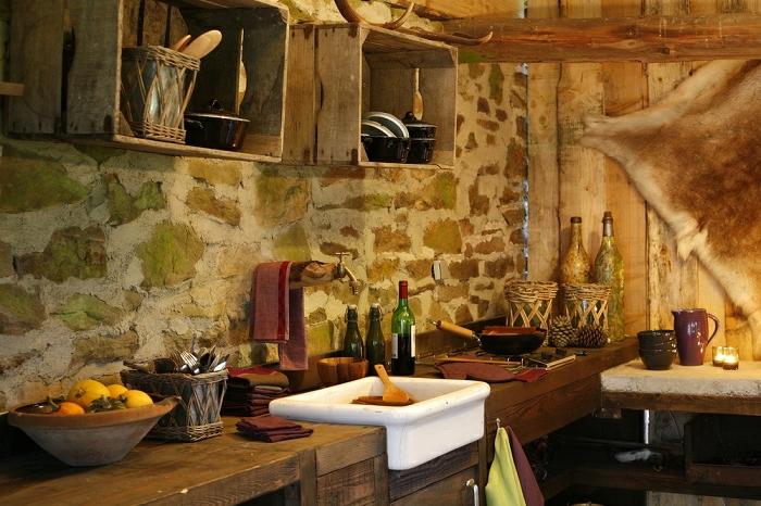 cuisine rustique, bol à fruits, murs en pierres, déco murale en faux fur, évier blanc, bouteilles, armoires en palettes