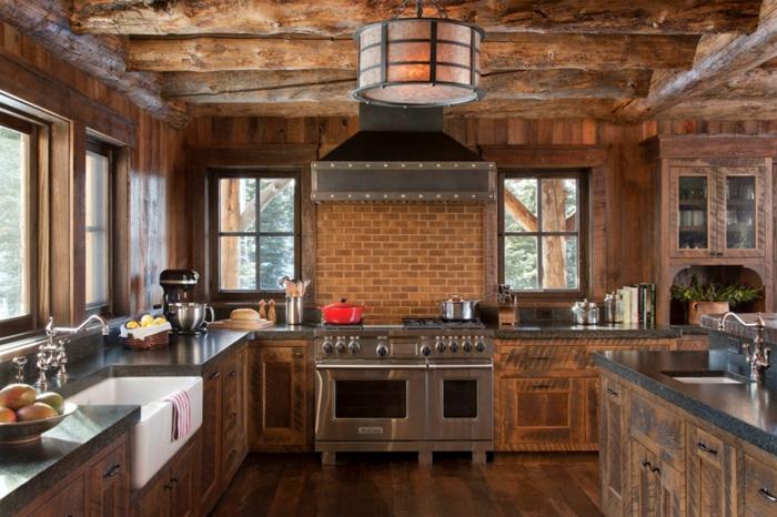 cuisine équipée, parquet en bois, lustre orange, casserole avec herbes vertes, bol aux fruits, évier de ferme blanc