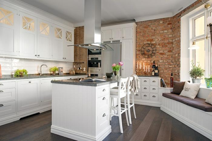 cuisine aménagée, armoires blanches en bois et verre, herbes vertes, bouquet de fleurs roses, bougeoirs, horloge