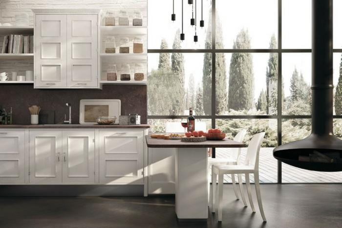 cuisine actuelle, mur blanc en brique, comptoir foncé, table à manger, chaises blanches, suspension luminaire avec ampoules électriques
