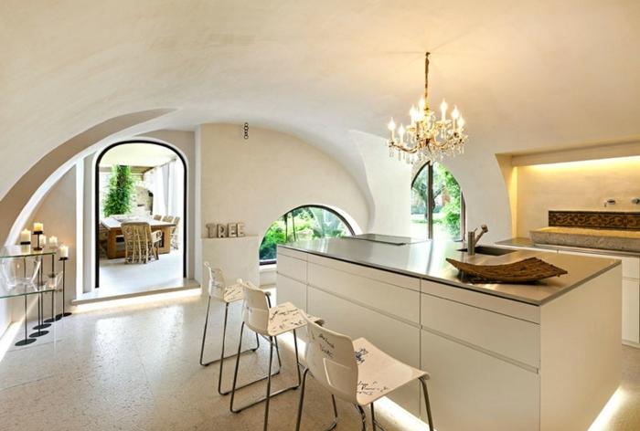 cuisine rustique, carrelage effet marbre, porte vers le jardin, lustre en bougies, chaises blanches, comptoir noir