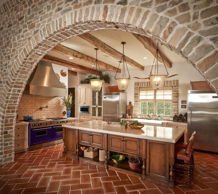 cuisine équipée, carrelage marron, mur en briques, plafond blanc, four électrique violette, réfrigérateur en argent