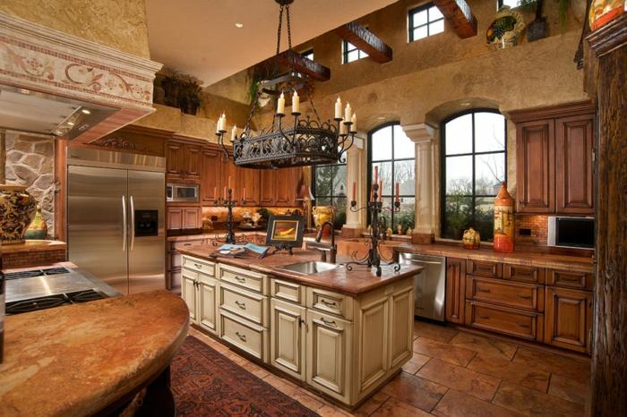 cuisine rustique, îlot centrale marron, bougeoir en fer forgé, poutre en bois, plantes vertes, modele de cuisine
