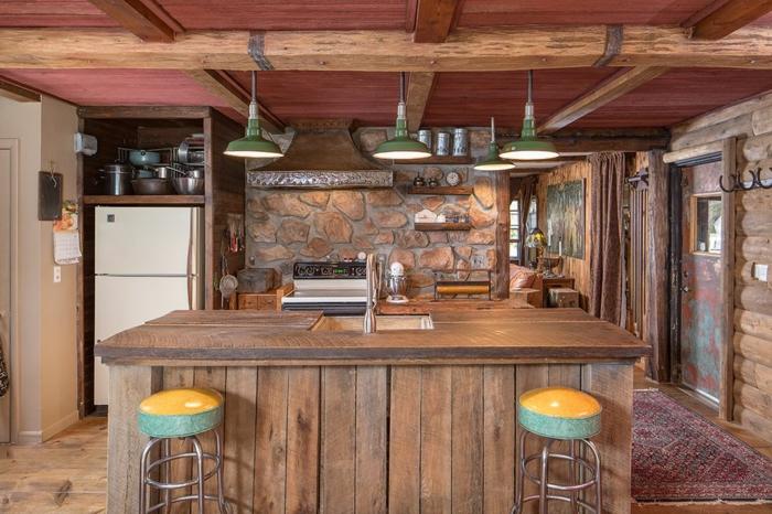cuisine équipée, réfrigérateur blanc, modele de cuisine, mur en pierre, lampes suspendues en vert, tapis ethnique