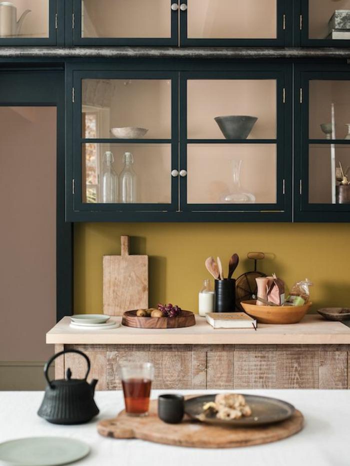 une crédence de cuisine peinte en ocre jaune tirant ver la couleur moutarde, association harmonieuse du bois et