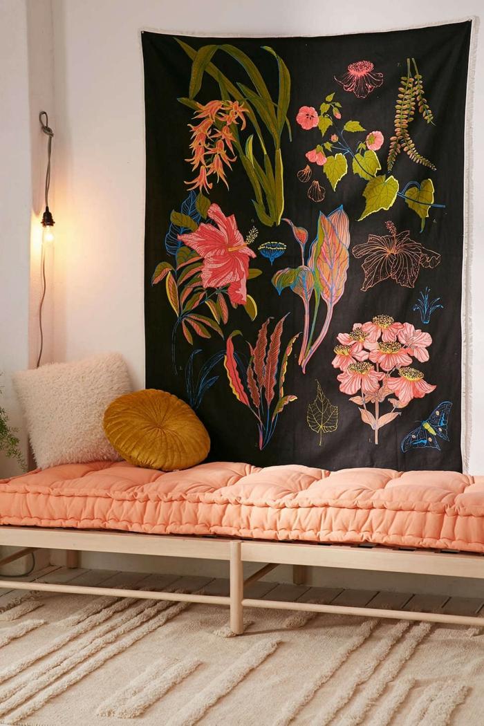 un coin repos d'ambiance bohème chic, canapé sans dossier rose de pêche décoré d'un coussin ronde couleur ocre jaune moutarde, tapis mural à motifs végétaux