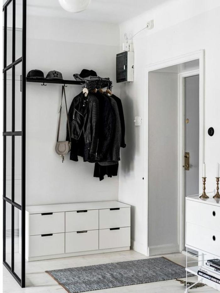 hall d'entrée maison avec meuble blanc aux cassettes de rangement et avec séparateur d'espace en métal noir