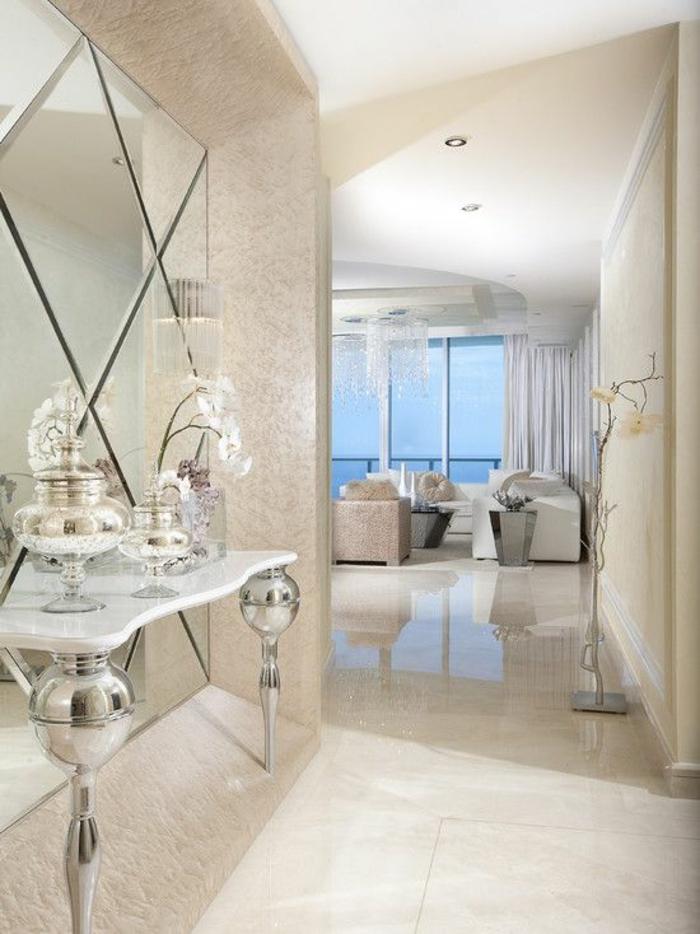 deco hall entree décor lumineux avec miroir réparti en losanges et table avec les pieds en métal couleur argent aux motifs boules brillantes