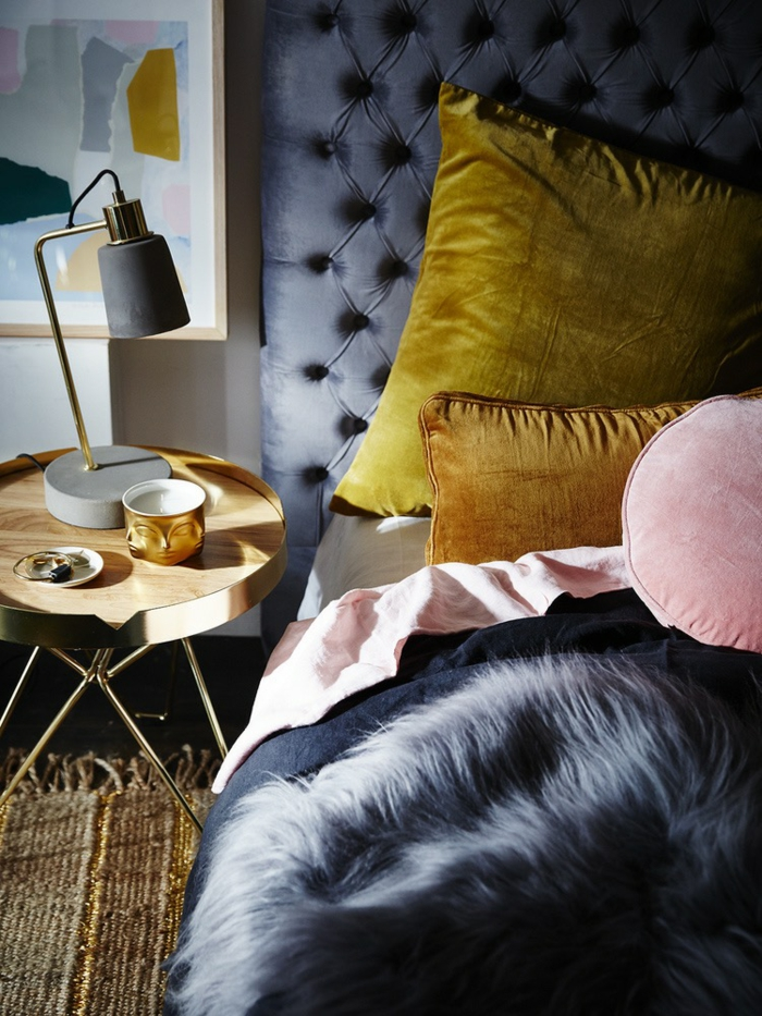 une chambre à coucher élégante aux teintes sombres du bleu dynamisée par des coussins ocre jaune et rose poudré