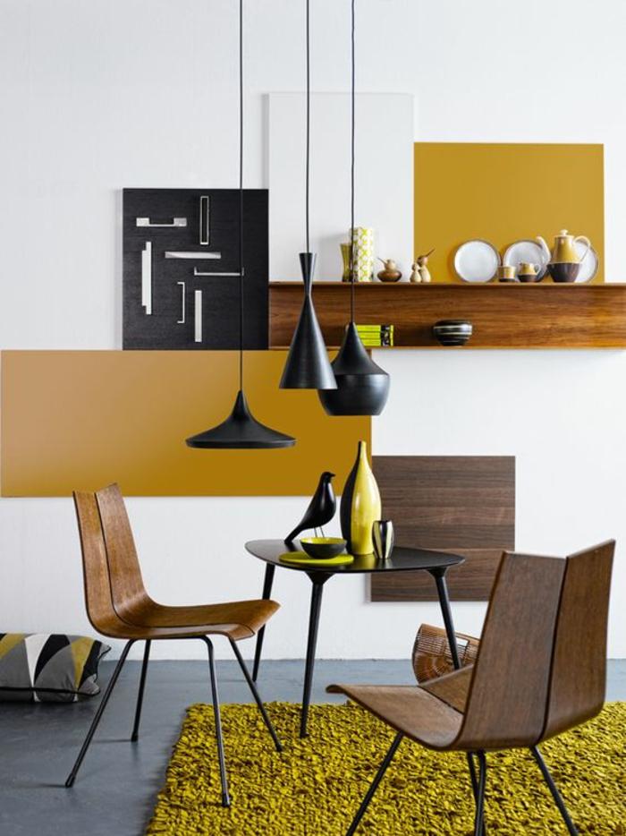 salon moderne de style scandinave qui met accent sur le bois foncé et la couleur jaune moutarde sur le mur et dans la déco