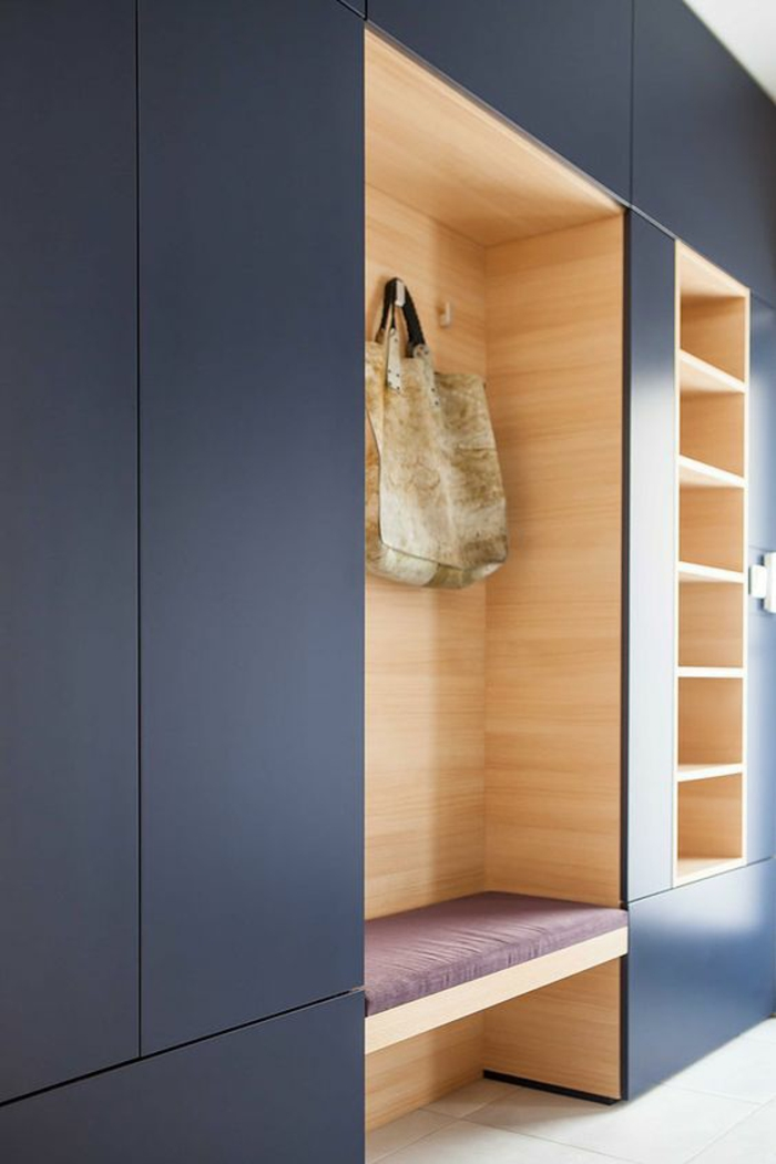 deco hall entree en bleu indigo avec coussin du banc en couleur lavande organisé en niches pour le porte-manteaux et pour le rangement des affaires