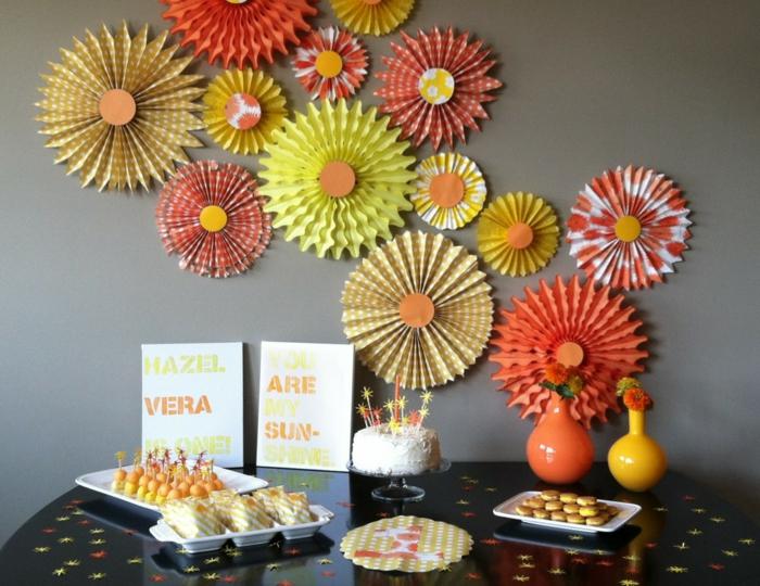 une composition de rosaces en papier soleil pour le buffet sucré, moulin à vent papier pour décorer le mur
