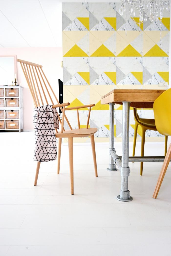 salle à manger scandinave ouverte sur le salon aux accents d'ocre doré et de bois naturel, pan de mur en papier peint géométrique