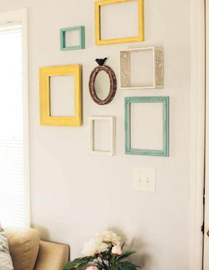 idée comment décorer un mur blanc de cadres vides ovales et rectangulaires formats et couleurs diverses, canapé fauve, plante