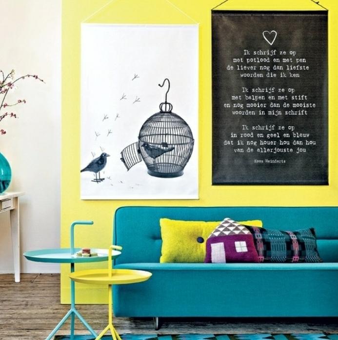 idee comment combiner la deco bleu canard avec le jaune, mur d accent et table jaune, canapé et tapis bleus, deco murale affiches en noir et blanc, dessin cagette d oiseau