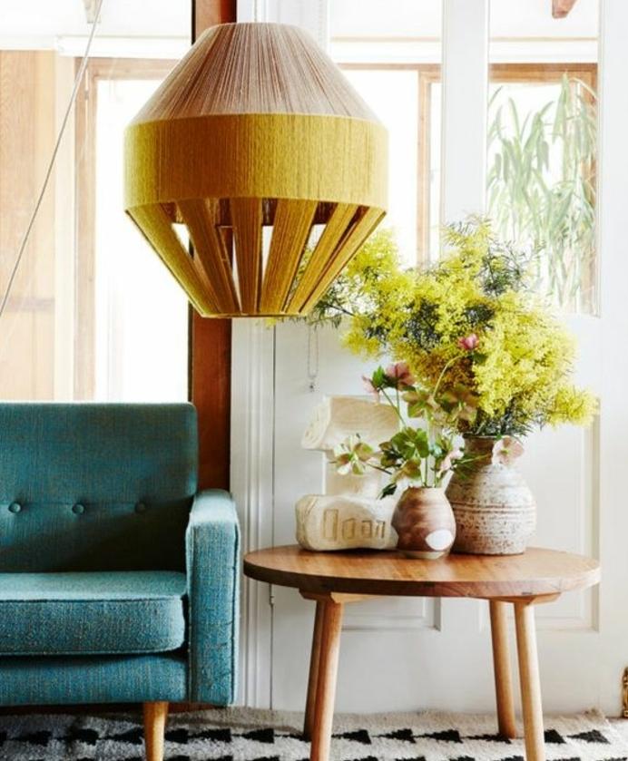 canapé deco bleu canard, suspension jaune orientale, table d appoint en bois, bouquet de fleurs, tapis blanc à triangles noirs