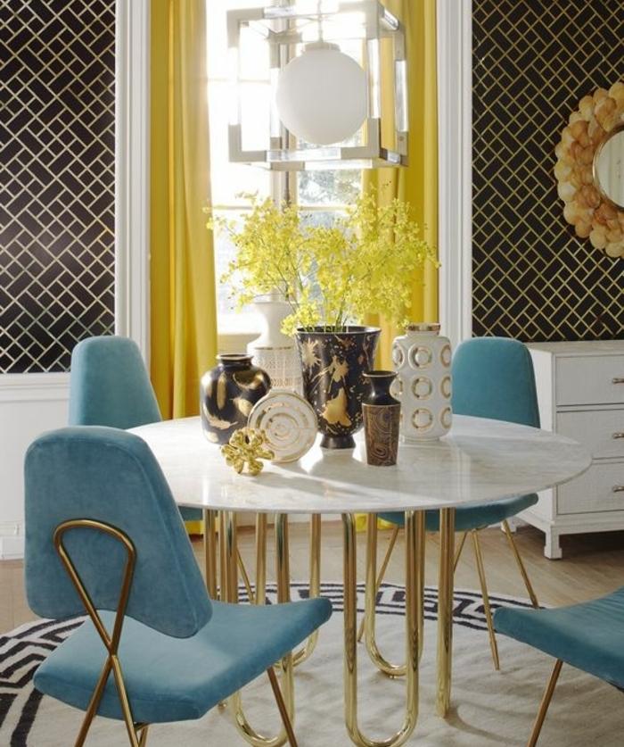 table en marbre et pieds dorés, chaises deco bleu canard, rideaux jaunes, mur à rectangles noirs, decoration orientale en jaune et bleu