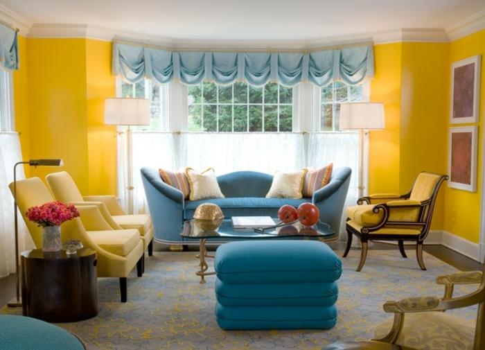 exemple de salon classique, mur couleur jaune imperial, avec des fauteuils jaunes, canapé et tabouret bleus, tapis gris, deco bleu et jaune