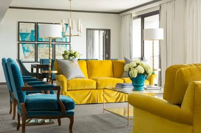 deco bleu et jaune salon élégant, canapé et fauteuil jaune, chaises en bois, coussin et dossier bleu canard, deco murale cartes géographiques, tapis gris