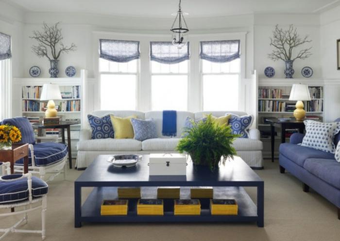 idée comment amenager un salon scandinave en blanc et bleu, deco bleu et jaune aux accents jaunes, deux canapés, chaises bleu et blanc, grandes table basse, bibliothèques de rangement livres