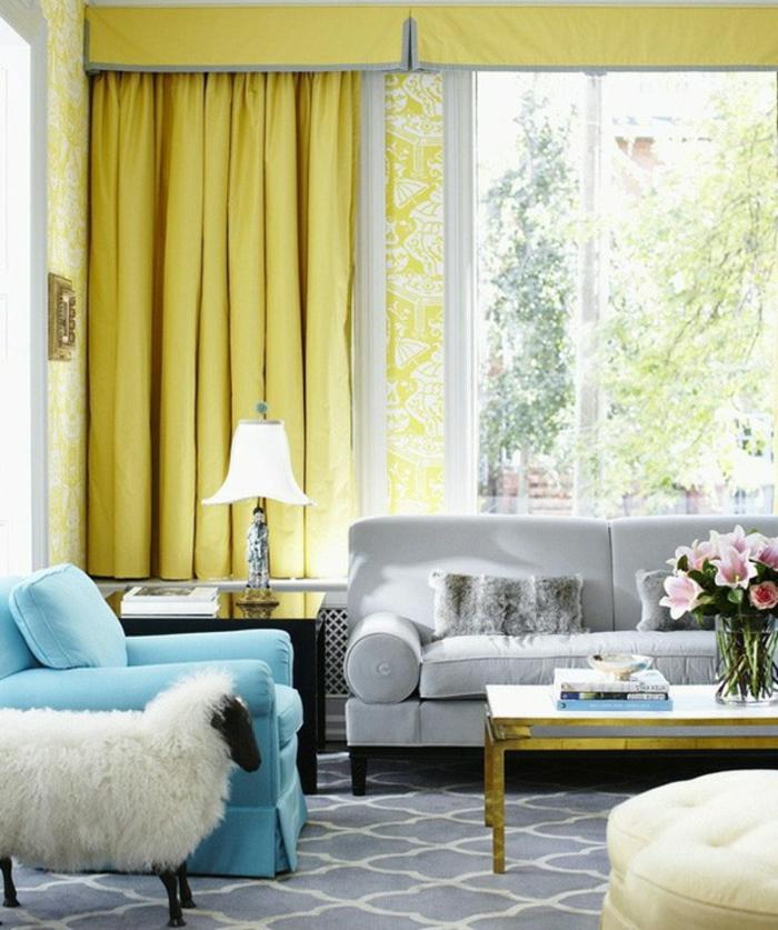 canapé gris, fauteuil bleu, tapis gris à motifs géométriques blancs, table basse, bouquet de fleurs, grande fenetre