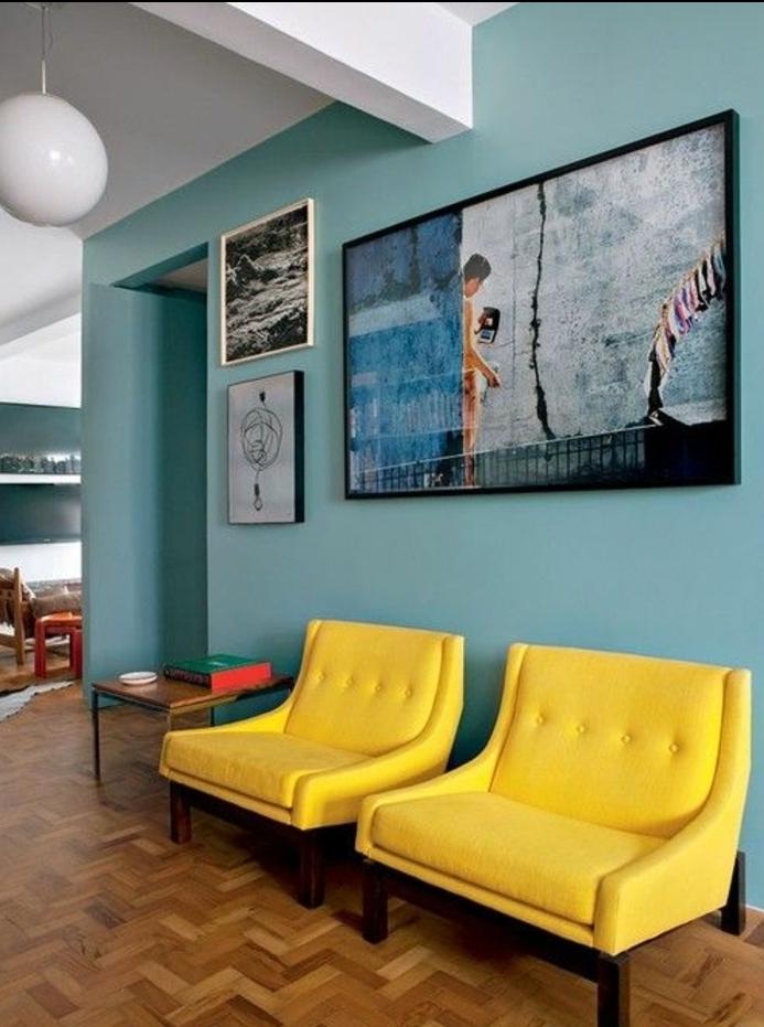idee deco bleu et jaune, tonalité pastel, fauteuils jaunes sur le fond d un mur décoré de tableaux artistiques, parquet clair