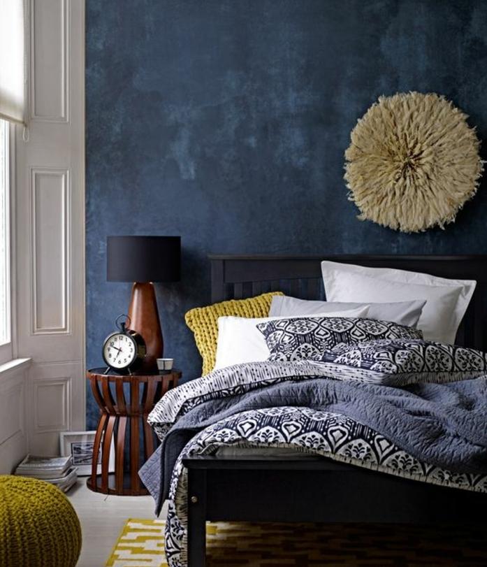 idée déco chambre adulte, lit noire, mur d accent bleu marine, coussin, pouf et tapis jaune, linge de lit motifs orientaux, deco murale intéressante, table de nuit en bois, réveil vintage