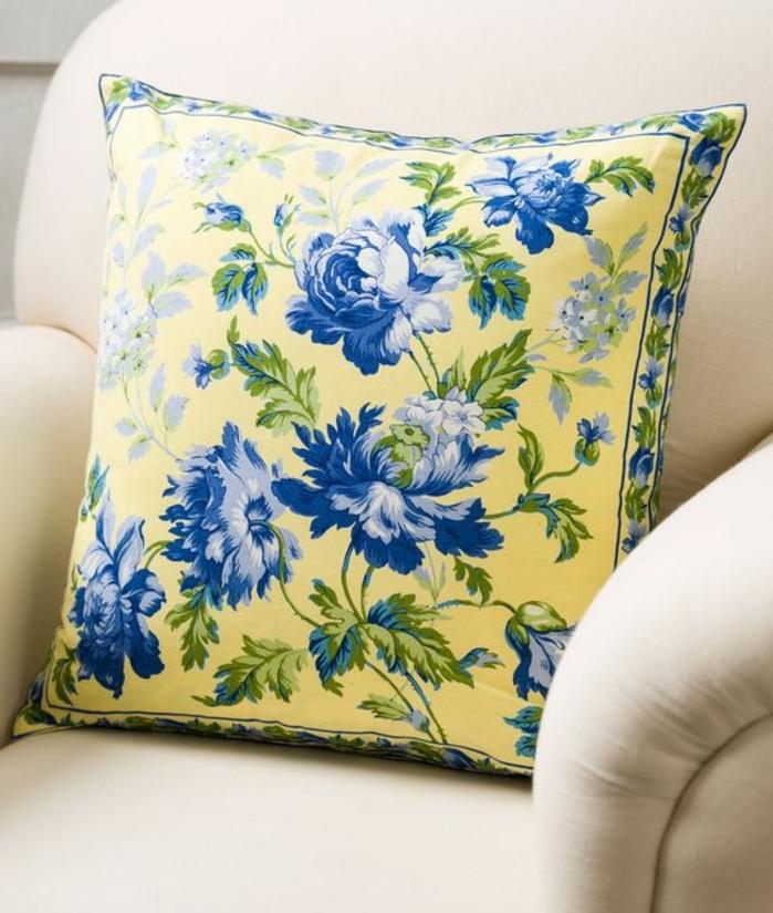joli accent deco bleu et jaune, coussin jaune a motifs fleurs bleues, fauteuil blanc cassé, decoration style shabby chic