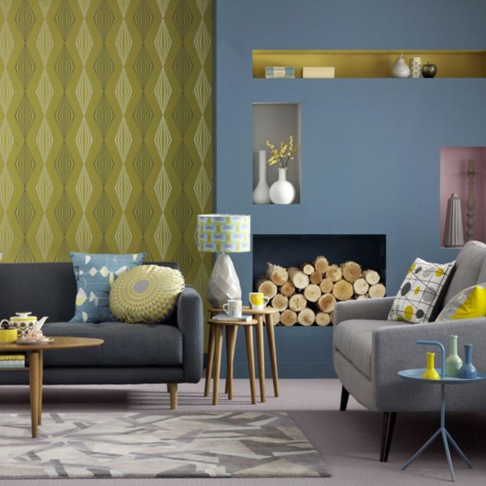 exemple deco bleu et jaune, canape gris anthracite et fauteuil gris, coussins multicolores, cheminée, table basse en bois, papier peint jaune et mur d accent bleu gris