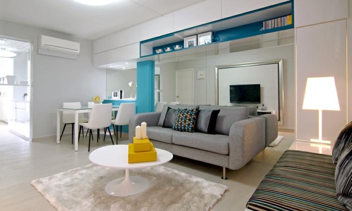 petits accents deco bleu et jaune, canapé gris, tapis blanc, table blanche, coin repas blanc, petite salle de séjour, appartement gain de place
