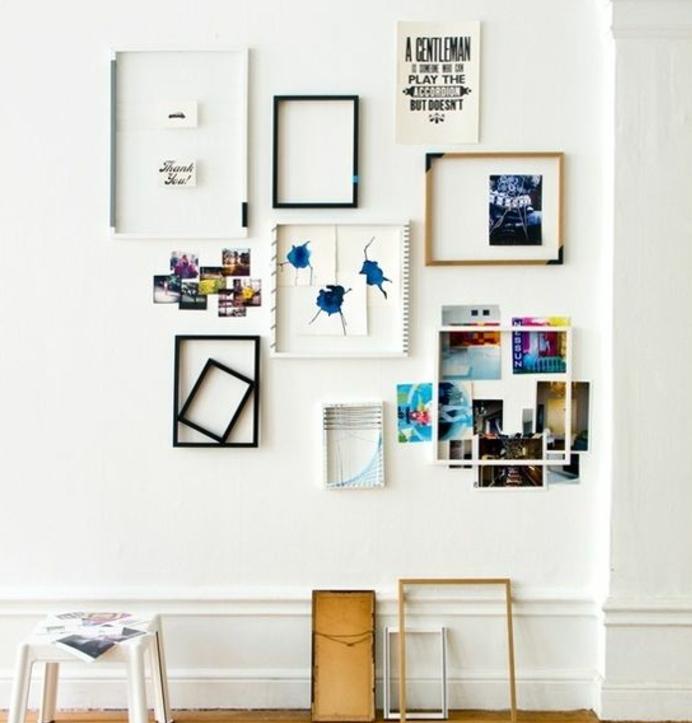 mur de cadres avec décoration hors cadre de photos pele mele superposées et dessins artistique, mur couleur blanche