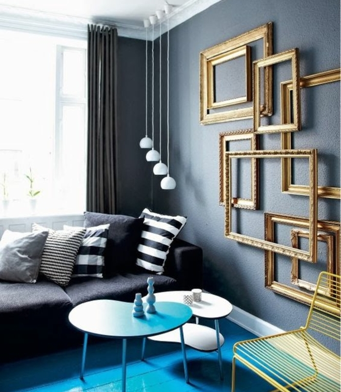 mur couleur grise et cadres formats divers superposés, tables gigognes bleu et blanc, canapé gris, coussins en gris, blanc et noir, petites suspensions blanches, idée de mur de cadres