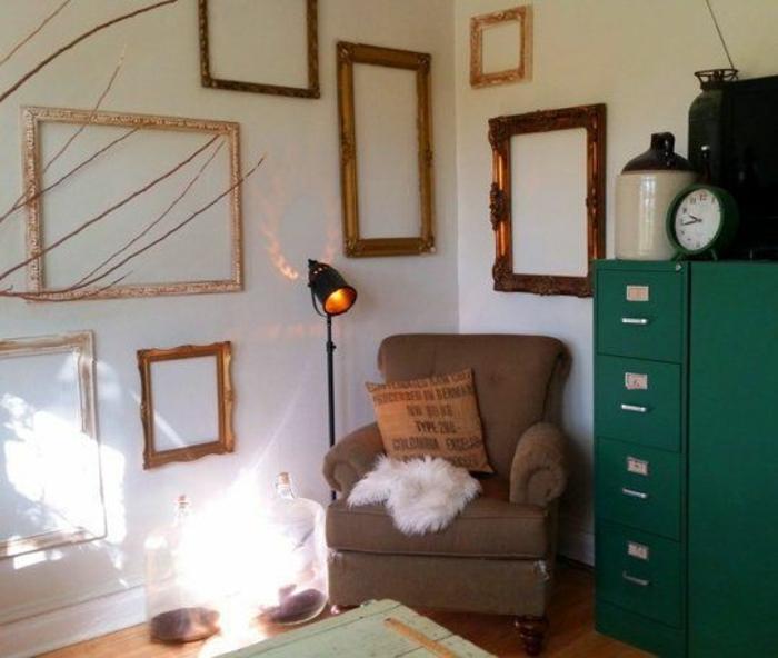 mur de cadres vintage formats divers, meuble de rangement vert, fauteuil marron, mur blanc, table en bois retro, disposition asymétrique
