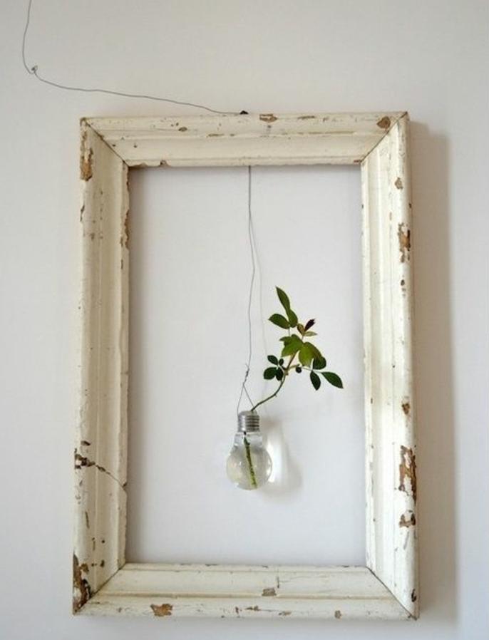 deco cadre vide aspect brut usé avec une ampoule éléctrique en guise de vase et branche verte dedans sur un fond blanc, decoration murale vintage rustique