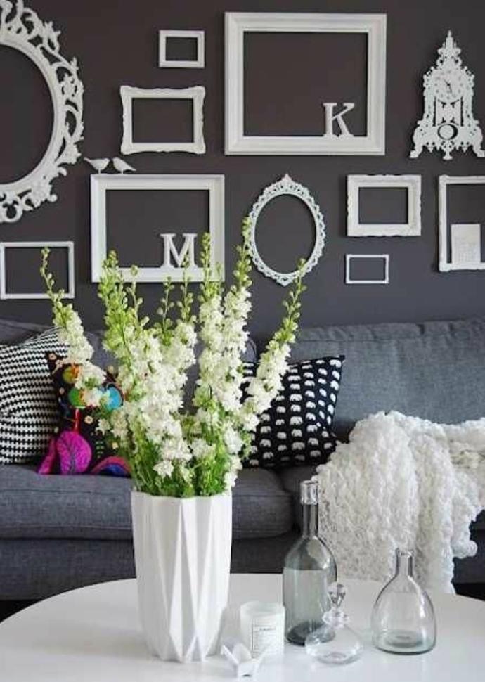 mur de cadres blancs vintage et lettres blanches décoratives, canapé gris, coussins multicolores, vase blanc, table blanche, bouquet de fleurs