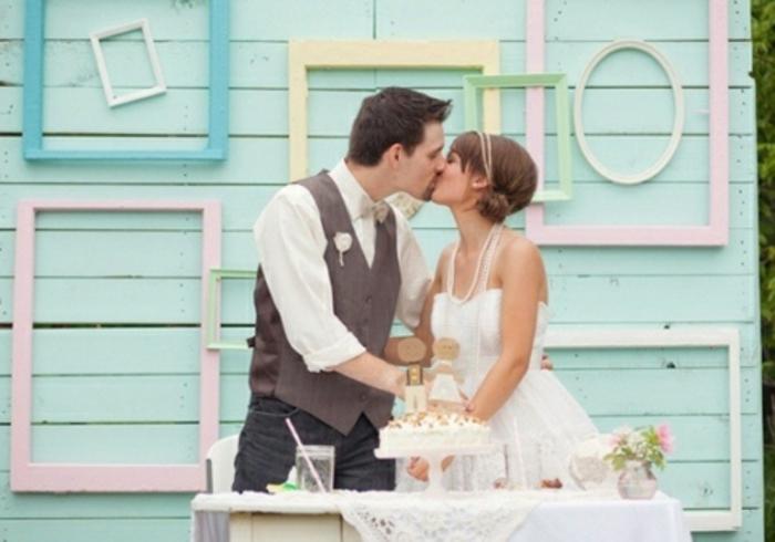 deco cadre vide mariage champetre chic, cadres formats diverse jaune, vert, rose et bleu, sur un mur de planches repeintes de vert, gateau de mariage, couple amoureux