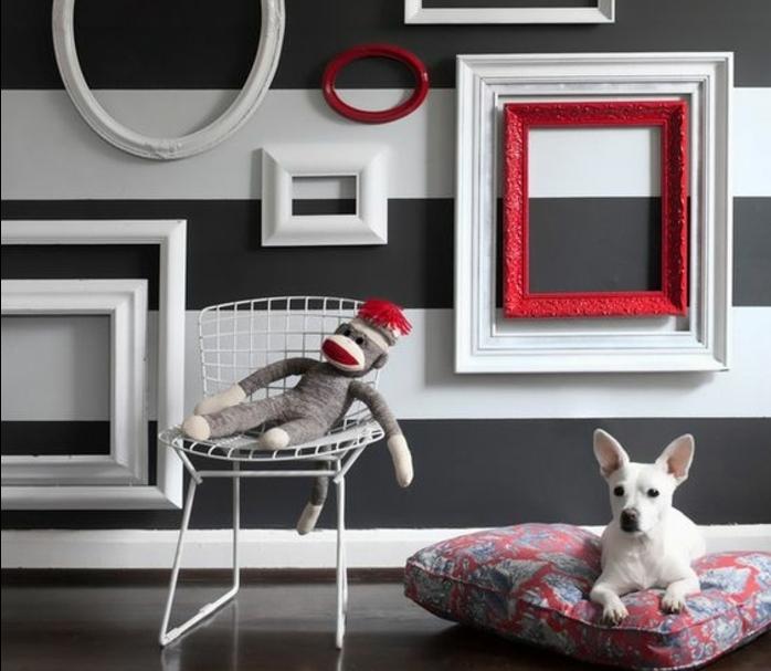 mur à rayures décorée de cadres vides ovales et rectangulaires en blanc et rouge, petit chien blanc sur un coussin, chaise en métal, jouet singe, habiller un mur