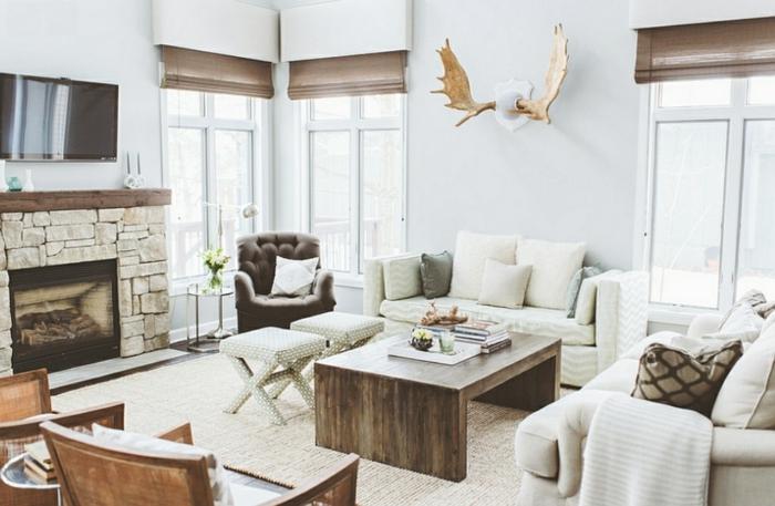 deco campagne chic et rustique à la fois, cheminee en pierre, table basse en bois, canapés blancs, chaises, fauteuil gris, tabourets blancs, deco bois de cerf