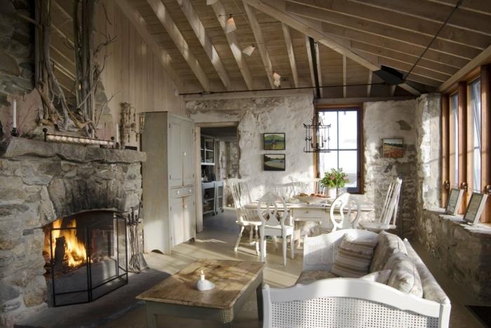 deco sejour campagne chic, table basse en bois, canapé blanc, cheminée en pierre, coin repas, chaises et table blanches, armoire grise